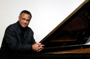 Pianist Andre Watts poses in front of a piano.