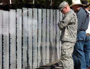 Veterans and community members read the names on the community memorial wall.